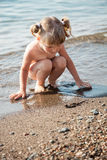 Pretty little girl playing on the seashore Stock Images