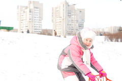 Pretty little girl playing with a sled in snow Royalty Free Stock Photos