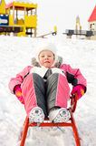 Pretty little girl playing on a sled in the snow Royalty Free Stock Photo