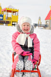 Pretty little girl playing on a sled in the snow Royalty Free Stock Image