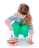 Pretty little girl playing with a spinning top Royalty Free Stock Image