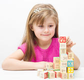 Pretty little girl playing with wooden cubes with letters and numbers. A Pretty little girl playing with wooden cubes with letters and numbers Stock Photography