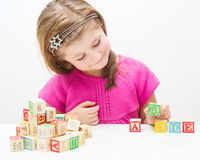 Pretty little girl playing with wooden cubes with letters and numbers. A Pretty little girl playing with wooden cubes with letters and numbers Royalty Free Stock Image