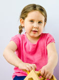 Pretty little girl plays with block puzzle Royalty Free Stock Images