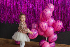 Pretty little girl plays with pink balloons. Pretty little girl plays with balloons royalty free stock photos