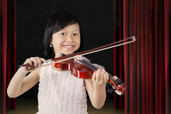 Pretty little girl plays violin on the stage Royalty Free Stock Photos