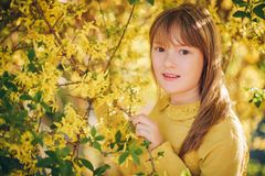 Outdoor fashion portrait of funny 9-10 year old girl. Pretty little girl portrait with spring blooming Forsythia flowers, wearing yellow blouse Royalty Free Stock Images