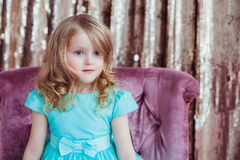 Pretty little girl. Pretty little girl posing against the golden background. Fashion photo. Christmas, birthday, party time Royalty Free Stock Photos