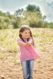 Pretty little girl posing at camera on riverside Stock Images