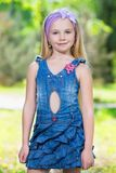 Pretty little girl. Posing in jeans dress outdoors Stock Image