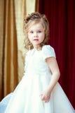 Pretty little girl posing in lush elegant dress Stock Images