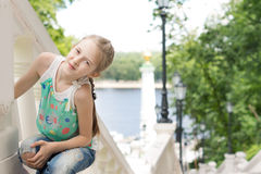 Pretty little girl posing on an outdoor staircase Royalty Free Stock Image