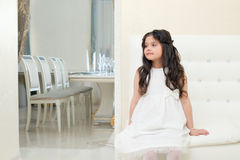 Pretty little girl posing while sitting on couch Stock Photo