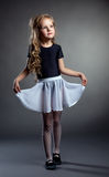 Pretty little girl posing straightened her skirt. On gray background Royalty Free Stock Photography