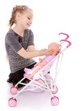 Pretty little girl puts her doll in a stroller Royalty Free Stock Image