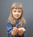 Pretty little girl reachs out empty palms. Grey background Stock Photo