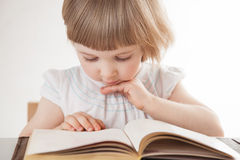 Pretty little girl reading a book Royalty Free Stock Photos