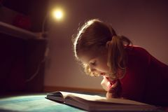 Pretty little girl reading book in her hiding place with flashli Royalty Free Stock Photo
