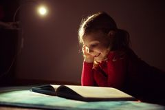 Pretty little girl reading book in her hiding place with flashli Stock Images