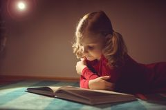 Pretty little girl reading book in her hiding place with flashli. Pretty little girl reading book in her hiding place under bed with flashlight at darkness Stock Photography