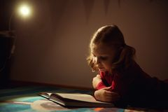 Pretty little girl reading book in her hiding place with flashli. Pretty little girl reading book in her hiding place under bed with flashlight at darkness Royalty Free Stock Photography
