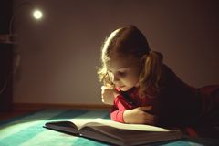 Pretty little girl reading book in her hiding place with flashli Stock Photos