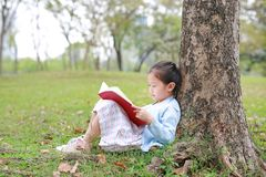 Pretty little girl reading a book sitting under a tree outdoor garden at summer day.  stock images