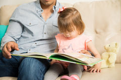 Pretty little girl reading with her father Royalty Free Stock Images