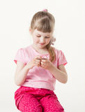 Pretty little girl reading the text on a card Royalty Free Stock Photography