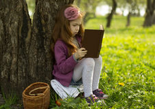 Pretty little girl reads book. In park Stock Images