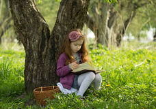 Pretty little girl reads book. In park Royalty Free Stock Photo