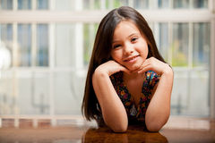 Pretty little girl relaxing at home. Portrait of a cute little Hispanic girl relaxing at home and smiling Stock Image