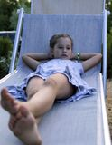 Pretty little girl resting on the deck at sunset Stock Photo