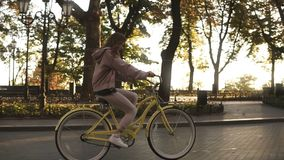 Pretty little girl riding yellow coloured bike on the street in summer city park. Trees and sunshines on the background stock video