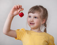 Pretty little girl with ripe strawberry. Neutral background Stock Image