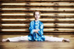 Pretty little girl in the room in sportswear for martial arts is royalty free stock photos