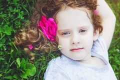 Pretty little girl with rose in her hair in green grass at summe Royalty Free Stock Image