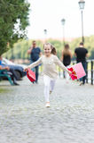 Pretty little girl running on street with pink shopping bags Stock Images