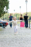 Pretty little girl running on street with pink shopping bags Royalty Free Stock Photos