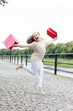 Pretty little girl running on street with pink shopping bags Royalty Free Stock Image