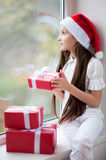 Pretty little girl in Santa hat dreaming by the window holding gift Stock Photography