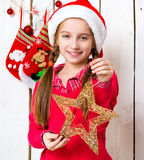 Pretty little girl in santa hat with star-toy in hands. In decorated room Stock Photo