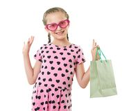Pretty little girl with shopping bag, studio portrait, dressed in pink with heart shapes, white background Royalty Free Stock Images