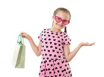 Pretty little girl with shopping bag, studio portrait, dressed in pink with heart shapes, white background Royalty Free Stock Photo