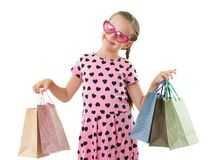 Pretty little girl with shopping bag, studio portrait, dressed in pink with heart shapes, white background Royalty Free Stock Photos
