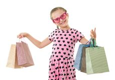 Pretty little girl with shopping bag, studio portrait, dressed in pink with heart shapes, white background Stock Photos