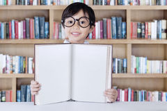 Pretty little girl showing book in library Stock Image