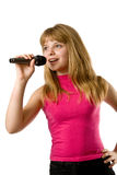 Pretty little girl singing in microphone. Isolated over white background Royalty Free Stock Photo