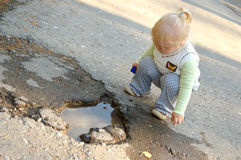 Pretty little girl sit near puddle in the park. Stock Photo