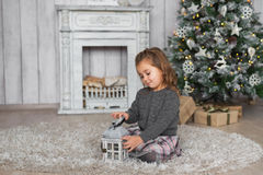 Pretty little girl sits on a floor and plays with wooden toy in Christmas at home Stock Photos